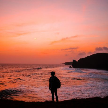 silhouette photo of man with backpack standing in seashore